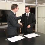 El Dr. Juan Carlos Mena y el Dr. Pablo Raúl Storni estrechando sus manos luego de haber suscripto el Convenio.